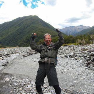 Triumphant after landing a trophy brown trout.