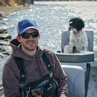 Head Guide and Fly fishing outfitter Max Yzaguirre with trusty boat dog Bessie.